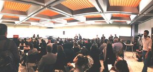 fotografia di un salone pieno di persone sedute che ascoltano un relatore